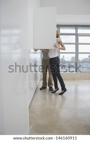 Full length side view of a couple looking in cupboard in empty apartment - stock photo