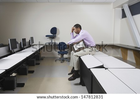 Full length side view of a depressed man sitting on desk with moving box - stock photo