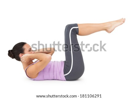 Full length side view of a fit young woman doing crunches over white background - stock photo