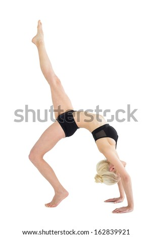 Full length side view of a fit young woman doing the wheel pose with one leg raised over white background - stock photo