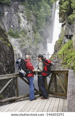 Full length side view of a man and woman near waterfall looking at each other - stock photo