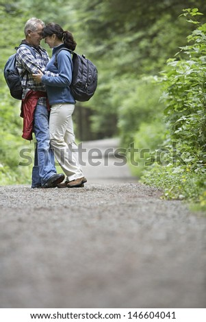 Full length side view of a middle aged couple embracing on forest road - stock photo