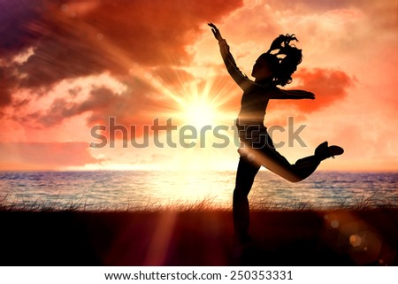 Full length side view of a sporty young blond jumping against sunrise over magical sea - stock photo