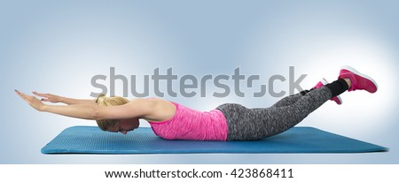 Full length side view of a sporty young woman stretching body in fitness studio - stock photo