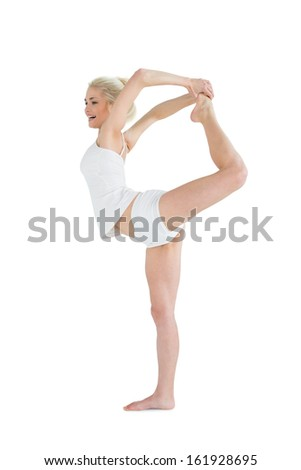 Full length side view of a sporty young woman stretching body while balancing on one leg over white background - stock photo