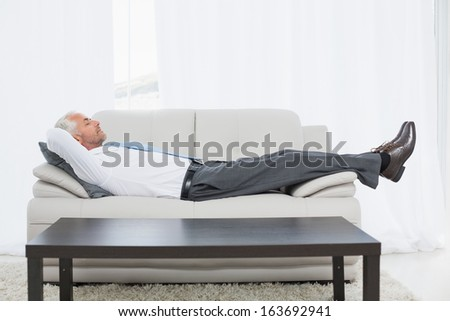 Full length side view of a tired mature businessman sleeping on sofa in the living room at home - stock photo