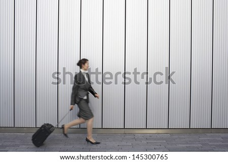 Full length side view of a young businesswoman walking with suitcase outdoors - stock photo