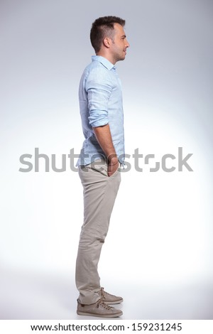 full length side view of a young casual man with both hands in his pockets. on gray background - stock photo