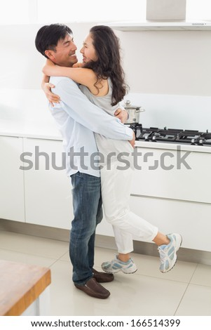 Full length side view of a young man embracing woman in the kitchen at home - stock photo