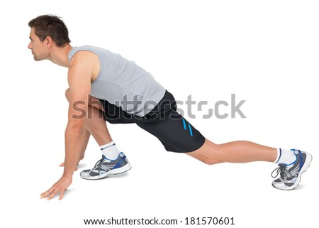 Full length side view of a young man in ready to run posture over white background - stock photo