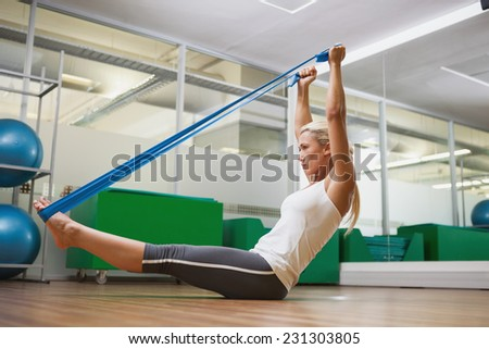 Full length side view of a young woman using resistance band in fitness studio - stock photo