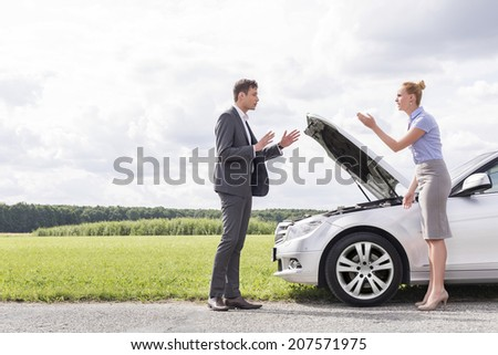 Full length side view of business couple arguing over broken car at countryside - stock photo