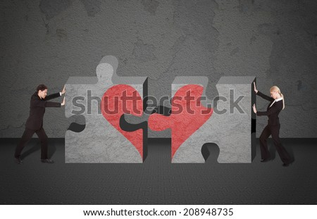 Full length side view of business people joining puzzle pieces with heart drawn on it - stock photo
