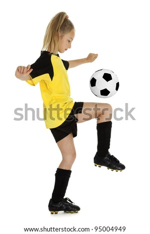 Full length side view of eight year old girl with soccer ball, isolated on white background. - stock photo