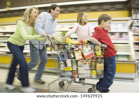 Full length side view of family of four running with full shopping trolley - stock photo