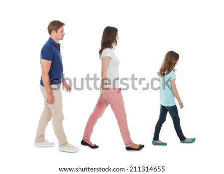Full length side view of family walking in a row isolated over white background - stock photo
