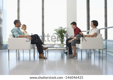 Full length side view of four business people sitting in modern waiting room at office - stock photo