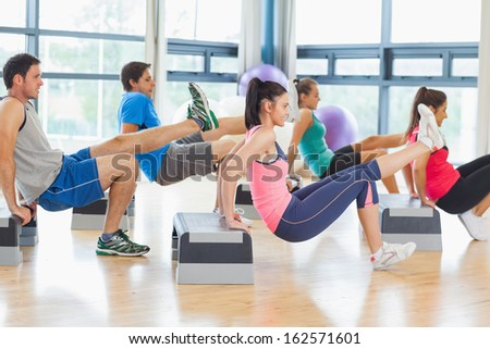Full length side view of instructor with fitness class performing step aerobics exercise in gym - stock photo