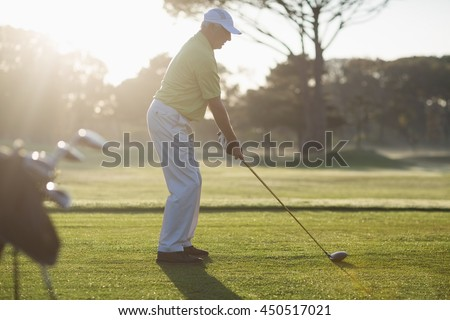 Full length side view of mature man playing golf while standing on field - stock photo