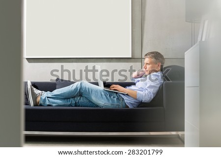 Full-length side view of Middle-aged man using laptop while lying on sofa - stock photo