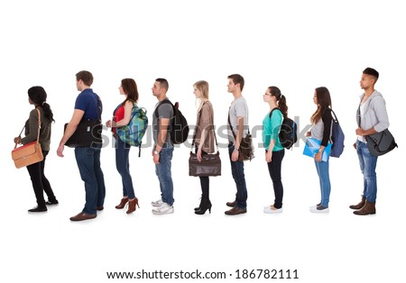 Full length side view of multiethnic college students standing in a row against white background - stock photo