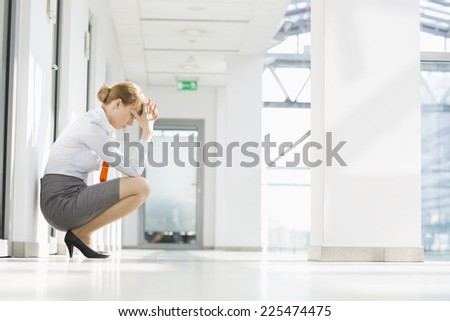 Full-length side view of stressed businesswoman crouching at office hallway - stock photo
