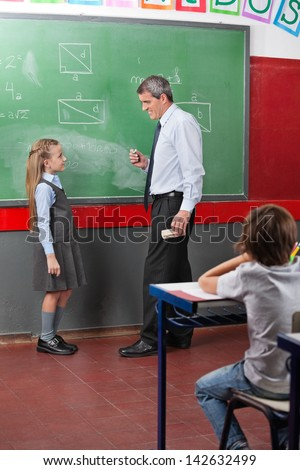 Full length side view of teacher and girl looking at each other while standing against board in classroom