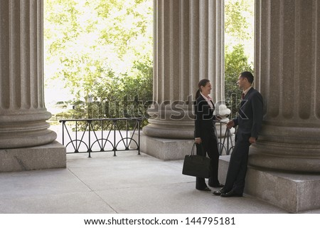 Full length side view of two attorneys talking at courthouse - stock photo