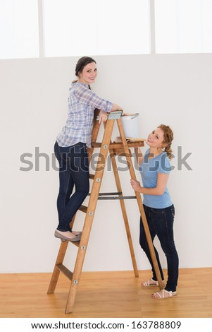 Full length side view of two cheerful female friends with a ladder in a new house