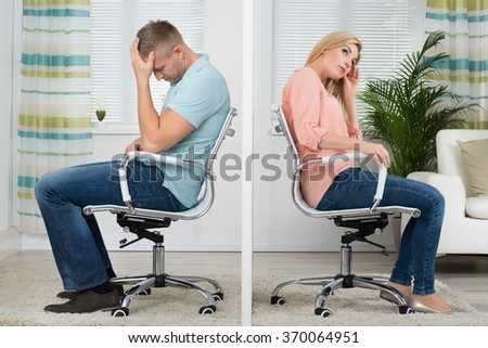 Full length side view of upset young couple sitting on chairs at home - stock photo