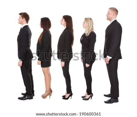 Full length side view of welldressed businesspeople standing in a line over white background - stock photo