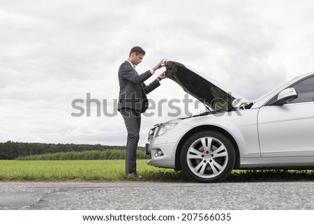 Full length side view of young businessman opening broken down car hood at countryside - stock photo