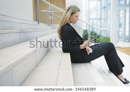 Full length side view of young businesswoman reading text message on office steps - stock photo