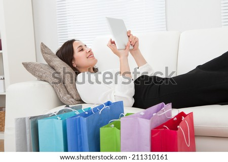 Full length side view of young businesswoman using digital tablet with shopping bags on floor at home - stock photo