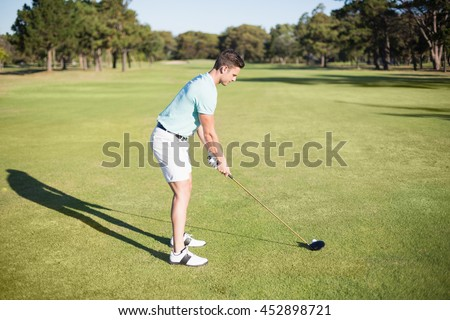 Full length side view of young man playing golf while standing on field - stock photo