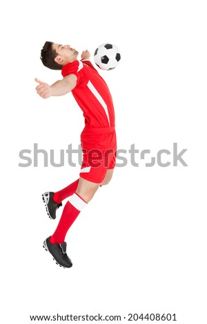 Full length side view of young player hitting soccer ball with chest over white background - stock photo