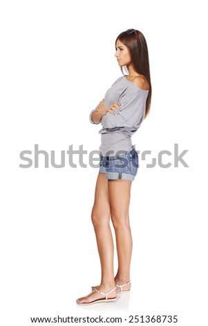 Full length side view of young stylish slim tanned female in denim shorts standing with folded hands looking forward seriously, isolated on white background - stock photo