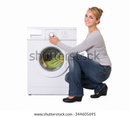 Full length side view of young woman crouching while using washing machine over white background - stock photo