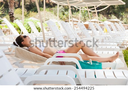 Full length side view of young woman in swimwear sunbathing on lounge chair at resort - stock photo