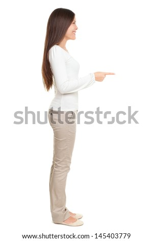 Full length side view of young woman pointing at copyspace isolated over white background - stock photo