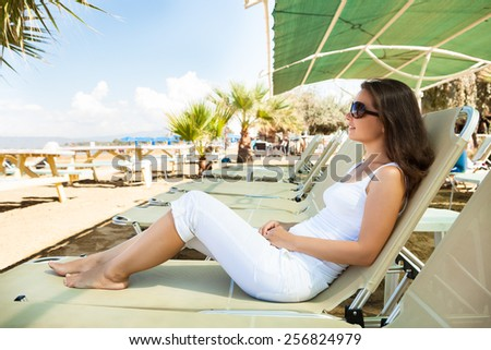 Full length side view of young woman relaxing on lounge chair at beach - stock photo
