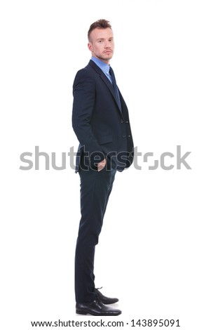 full length side view picture of a young business man looking at the camera while holding his hands in his pockets. on white background