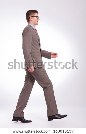 full length side view picture of a young business man walking forward. on a gray background