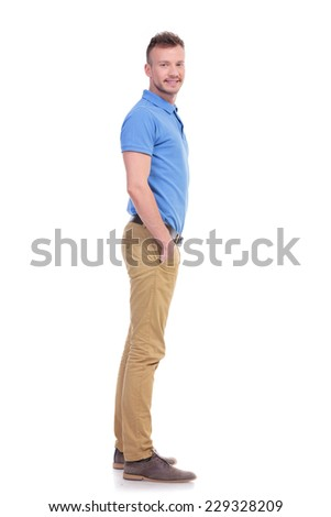 full length side view picture of a young casual man looking into the camera while holding his hands inside his pockets and smiling. isolated on a white background - stock photo