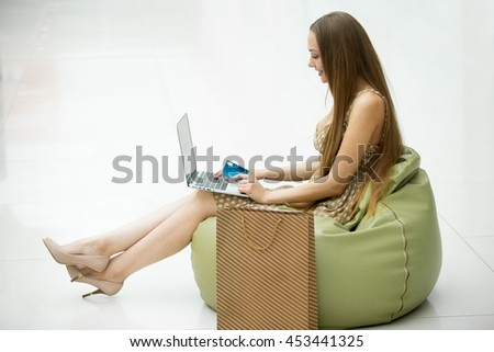 Full-length side view portrait of young smiling pretty woman sitting in shopping centre on bean bag chair with laptop on her knees and holding credit card in hand, shopping online. White background - stock photo