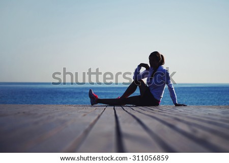 Full length silhouette of skinny female athlete resting after an active run while sitting on the wooden pier against ocean beach, woman runner with good figure resting after an active fitness training - stock photo