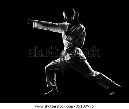 full-length silhouette portrait of beautiful martial arts girl in kimono exercising karate kata on black