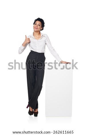 Full length smiling business woman standing leaning at blank white board gesturing thumb up, isolated on white background - stock photo
