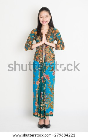 Full length Southeast Asian woman with batik dress in greeting gesture standing on plain background. - stock photo