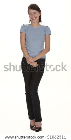 Full length studio photo of pretty young woman standing, smiling, looking at camera. White background. - stock photo